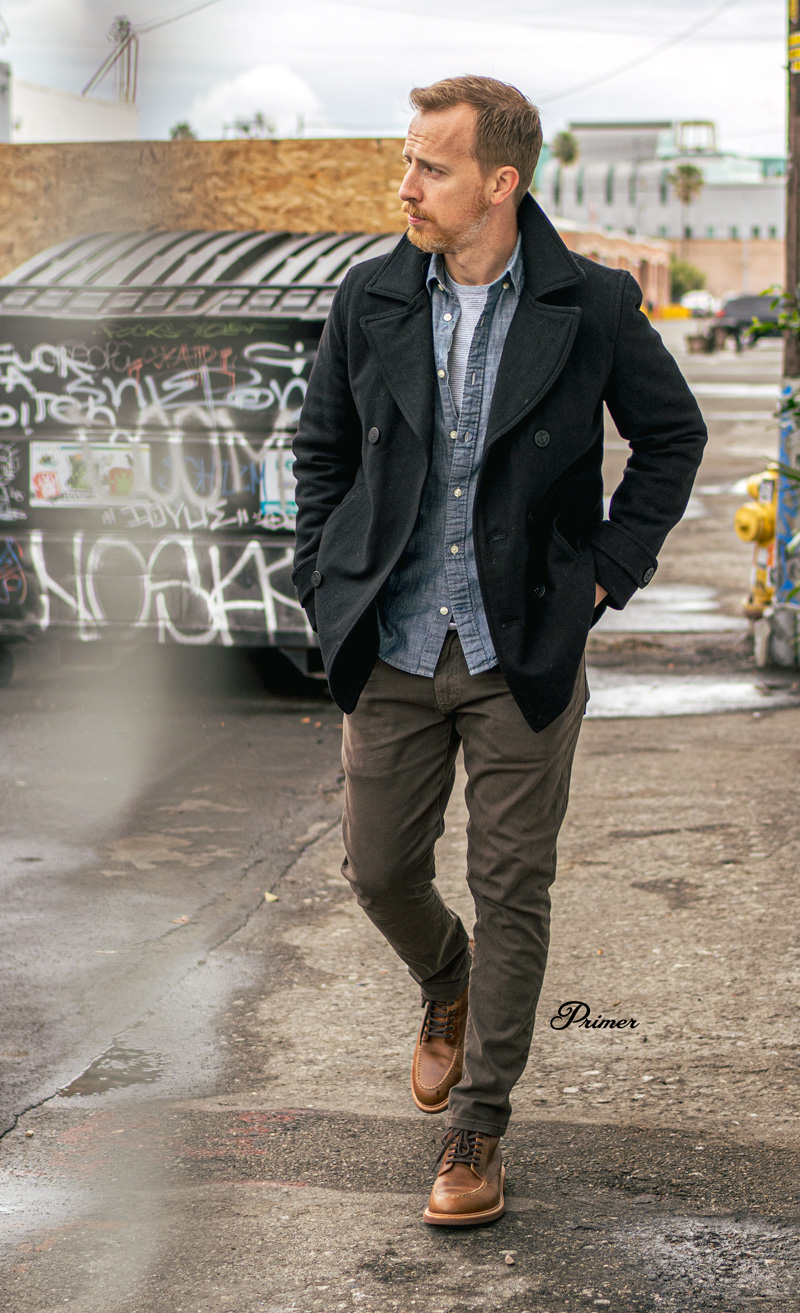 man wearing casual outfit idea rugged pea coat, chambray shirt, pocket tee, twill pants, moc toe boots