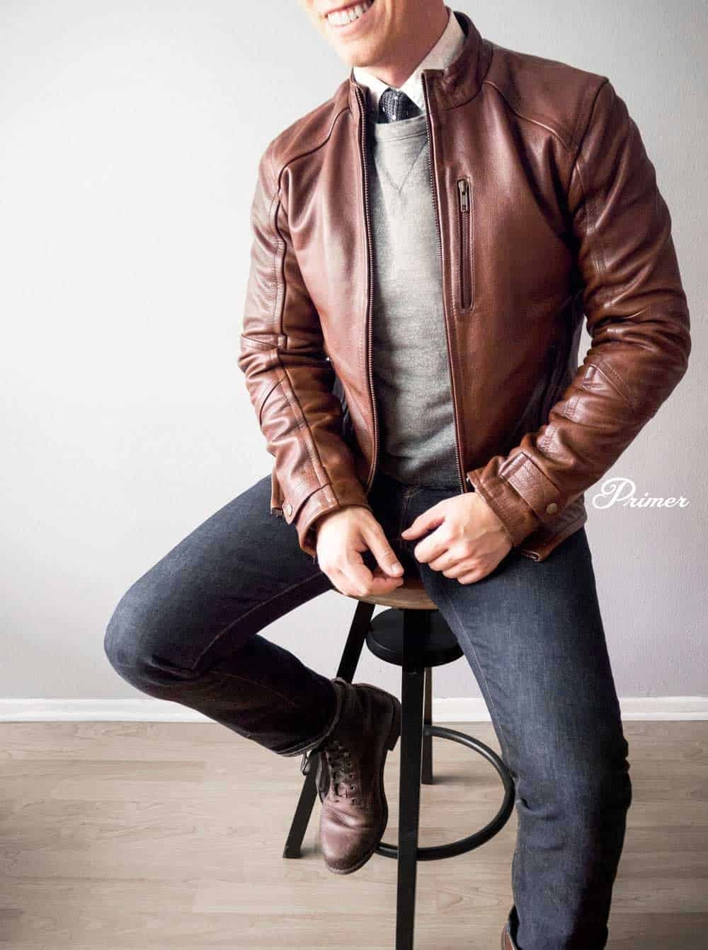 man wearing a brown leather jacket and blue denim jeans