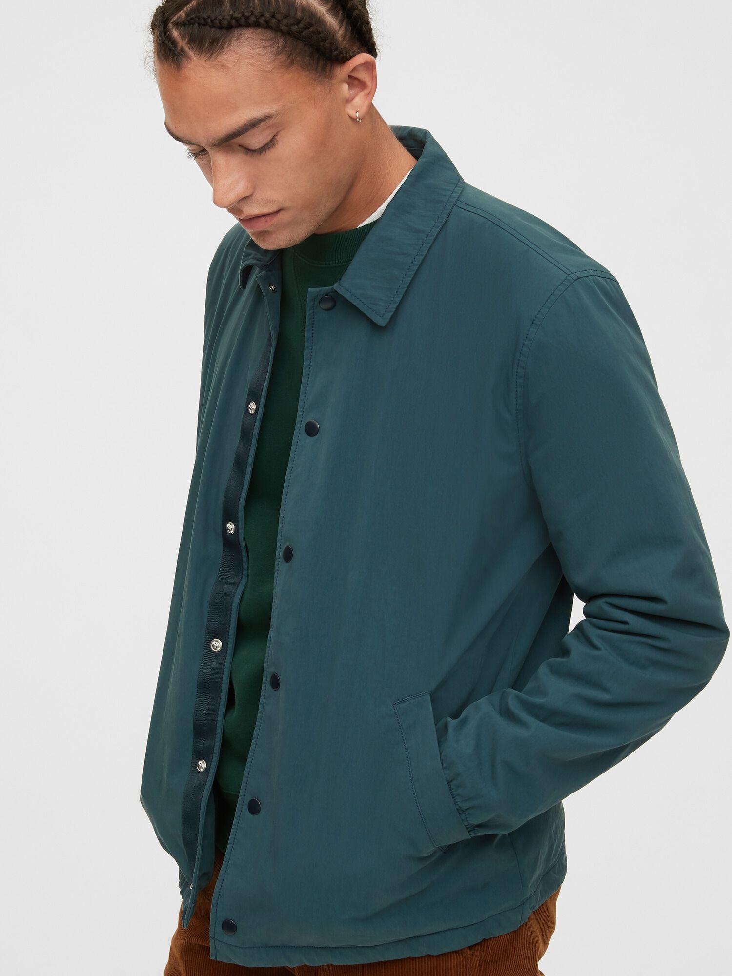 a man wearing a teal coach jacket