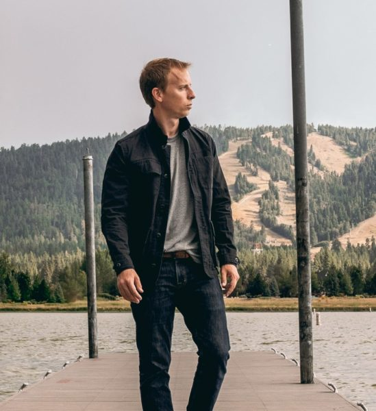 man standing on a pier wearing a jacket and jeans