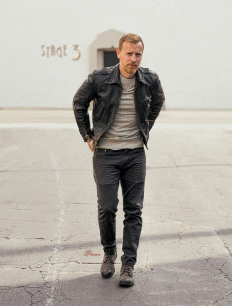 Andrew Snavely wearing black leather jacket, gray sweatshirt, charcoal jeans, gray boots monochrome outfit inspiration
