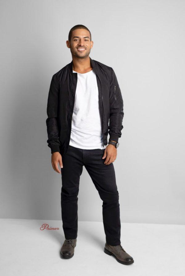 man wearing a black bomber jacket and black pants