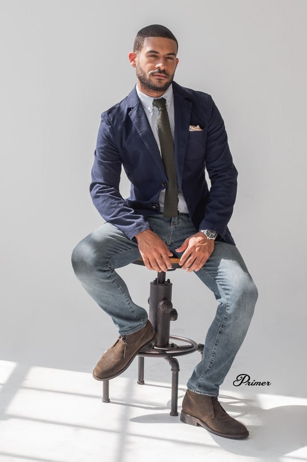 man wearing a blue navy blazer and blue jeans