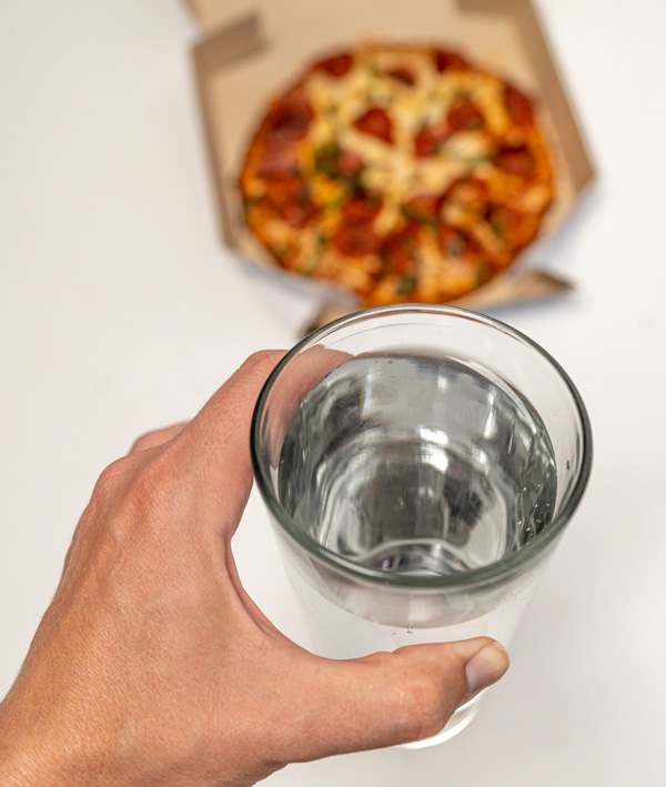 holding a glass of water in front of a pizza
