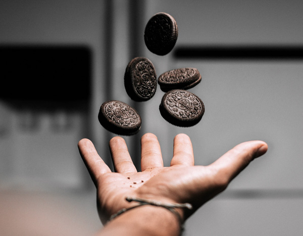 hand catching 5 oreo cookies