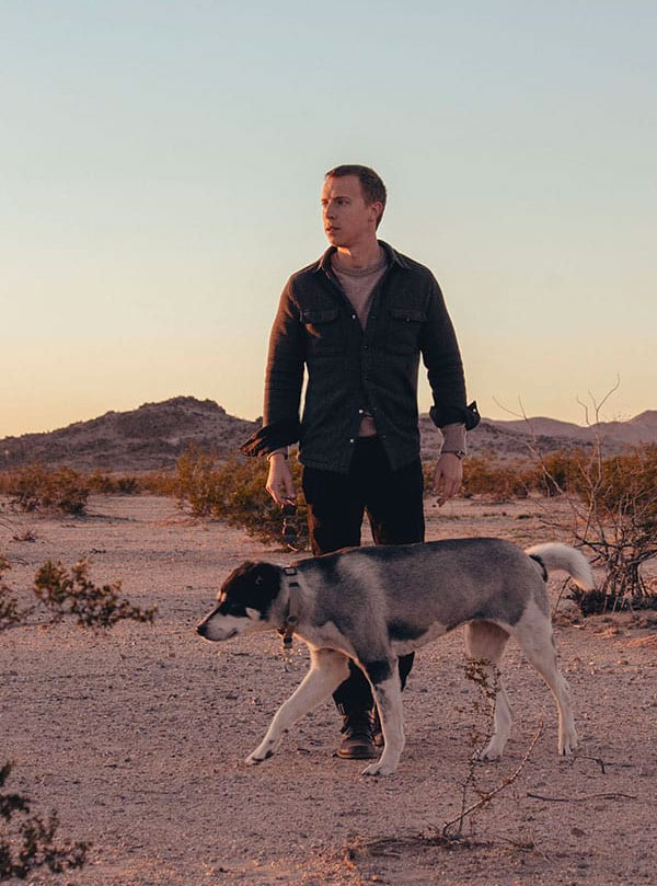 shirt jacket outfit with cashmere sweater and black jeans - man and dog in desert
