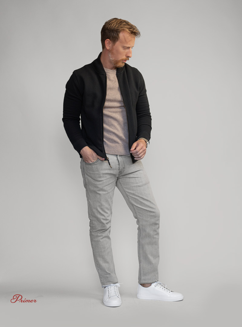 Smart casual outfit with black bomber, tan sweater, gray jeans, and white sneakers