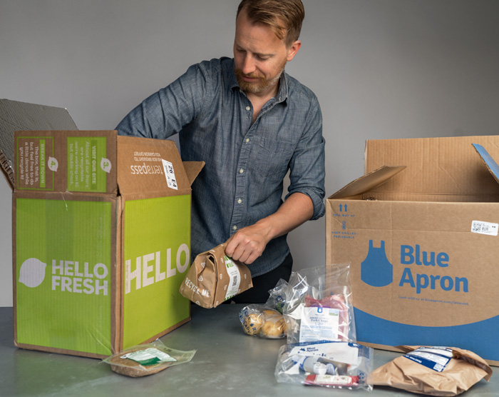man taking items out of hello fresh and blue apron subscription boxes