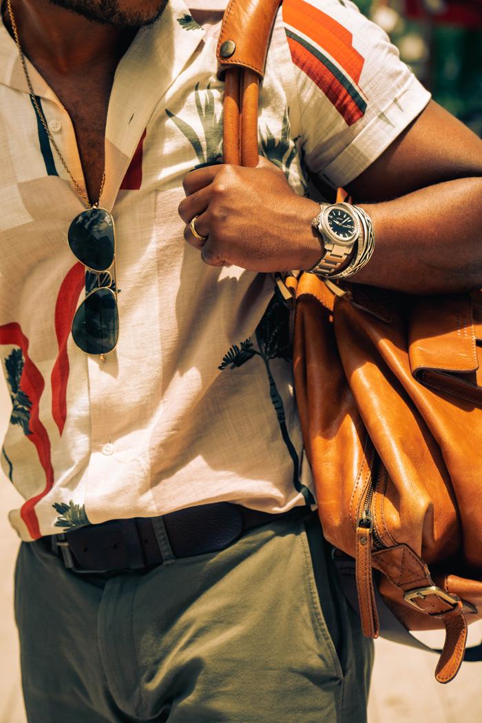 detail shot of camp collar shirt, sunglasses, watch, and weekender bag