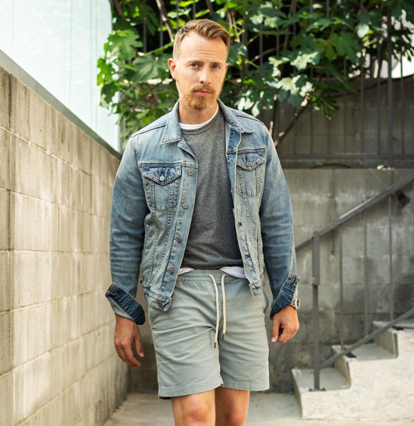 man wearing light blue denim trucker jacket with gray t-shirt and green drawstring shorts in summer