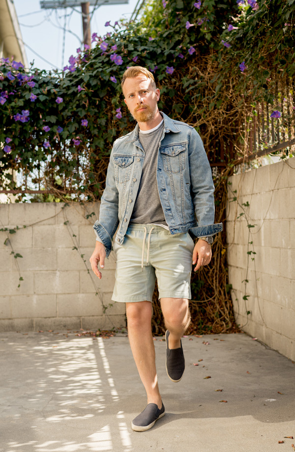 men's casual summer outfit idea with denim jacket, t-shirt, drawstring shorts, and slip on sneakers
