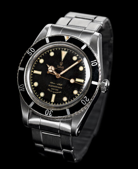 watch with silver metal link and black and gold face