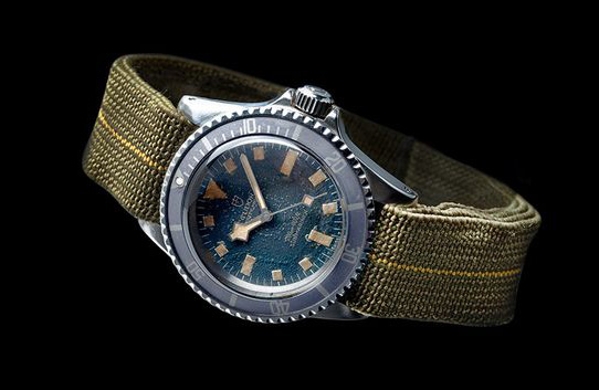 watch with green strap and silver and blue face