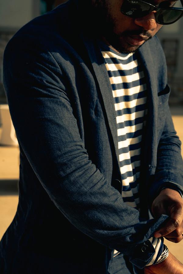 Daniel Baraka rolling the sleeves of his suit jacket