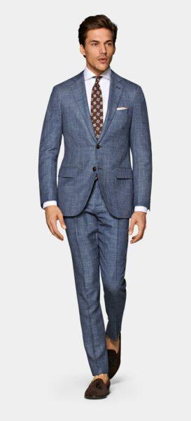 man wearing a blue suit jacket and blue suit pants