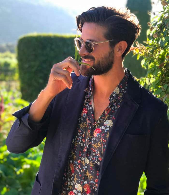 man at summer wedding wearing a floral shirt and blue blazer
