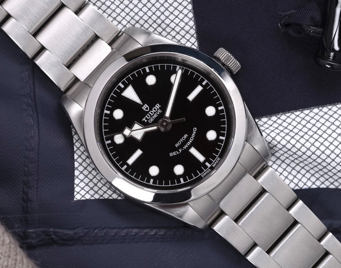 watch with silver link band and black and silver face