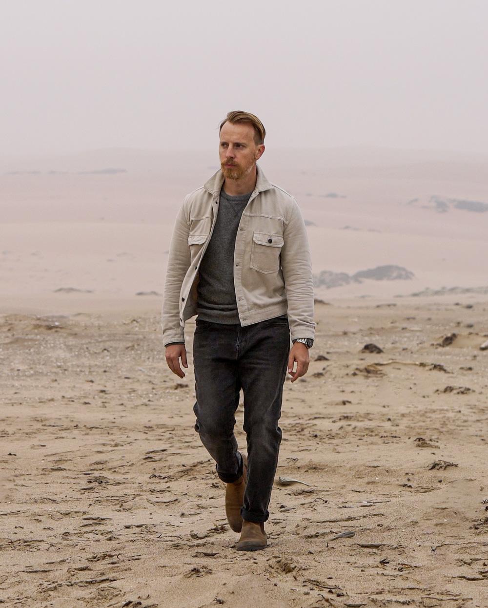 man in desert wearing Buck Mason trucker jacket, J.Crew gray sweatshirt, Goodthreads jeans, Thursday boots