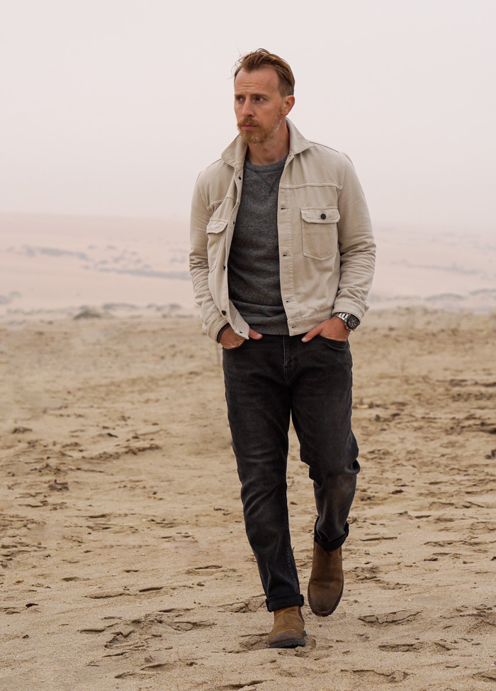 men's fall outfit with tan trucker jacket, grey sweatshirt, faded black jeans, and brown Chelsea boots –Primer
