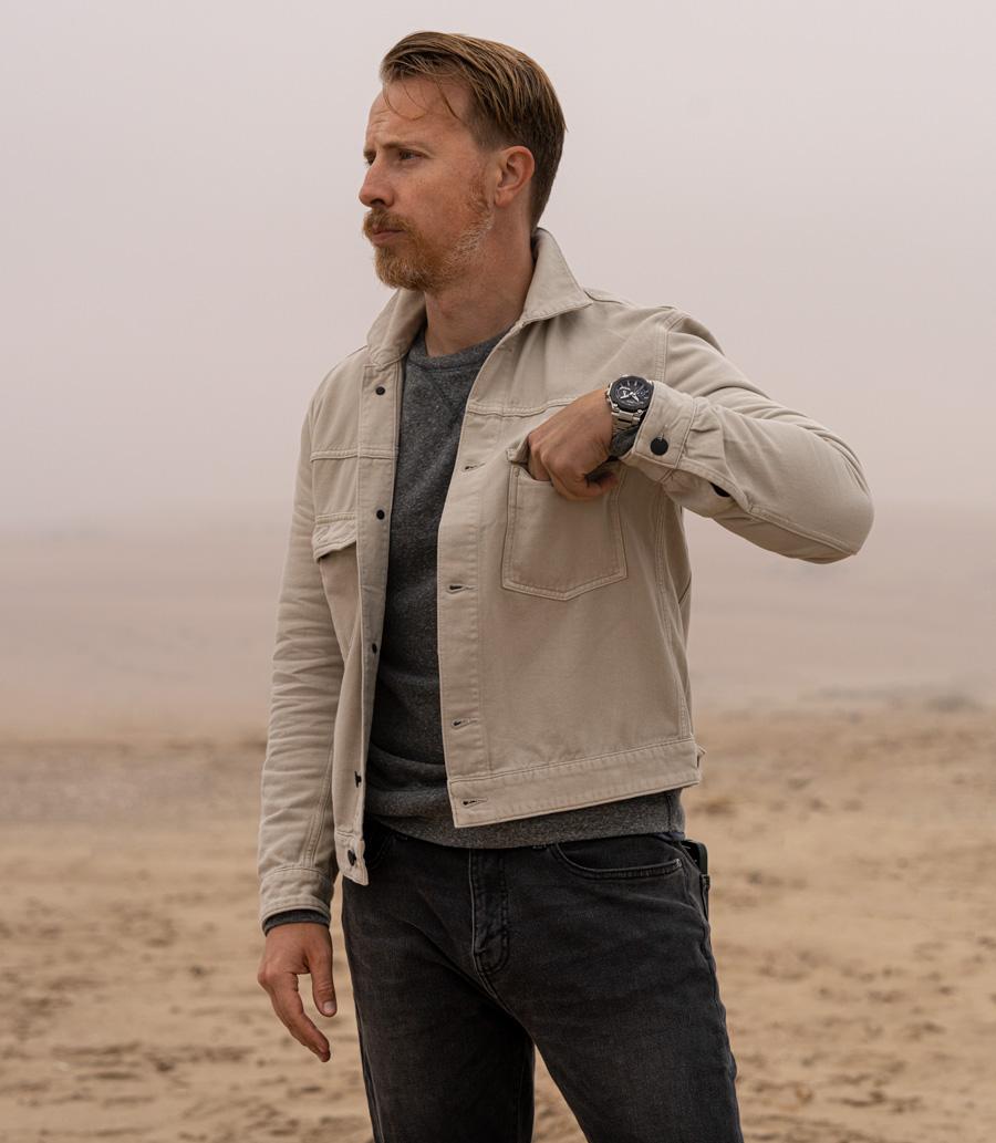 Man wearing G-Shock MTG Watch with tan trucker jacket, grey sweatshirt, and faded black jeans in desert