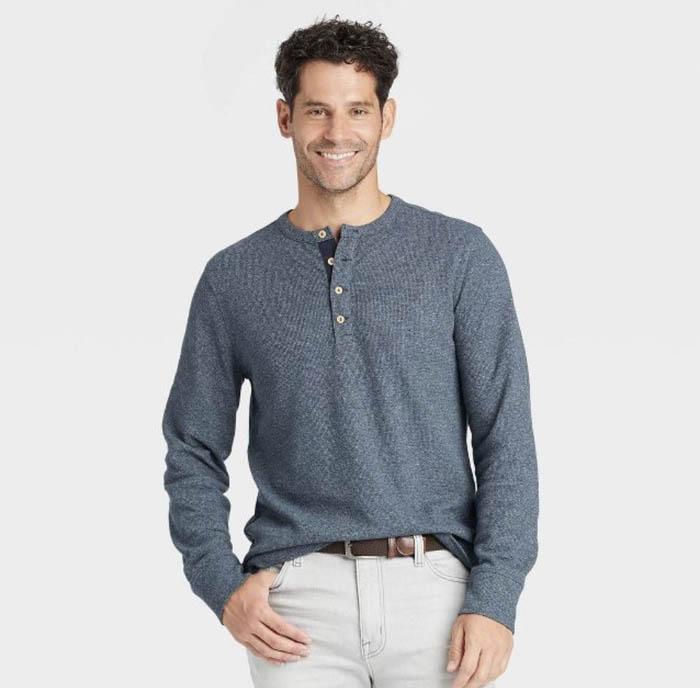 man wearing a light grey blue long sleeve henley shirt
