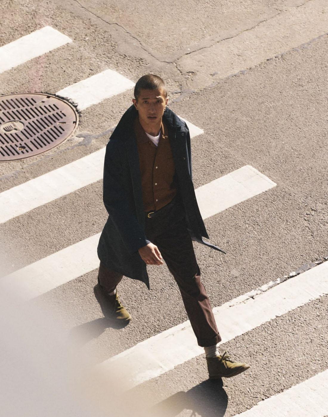 man using a crosswalk to cross a street wearing a long coat