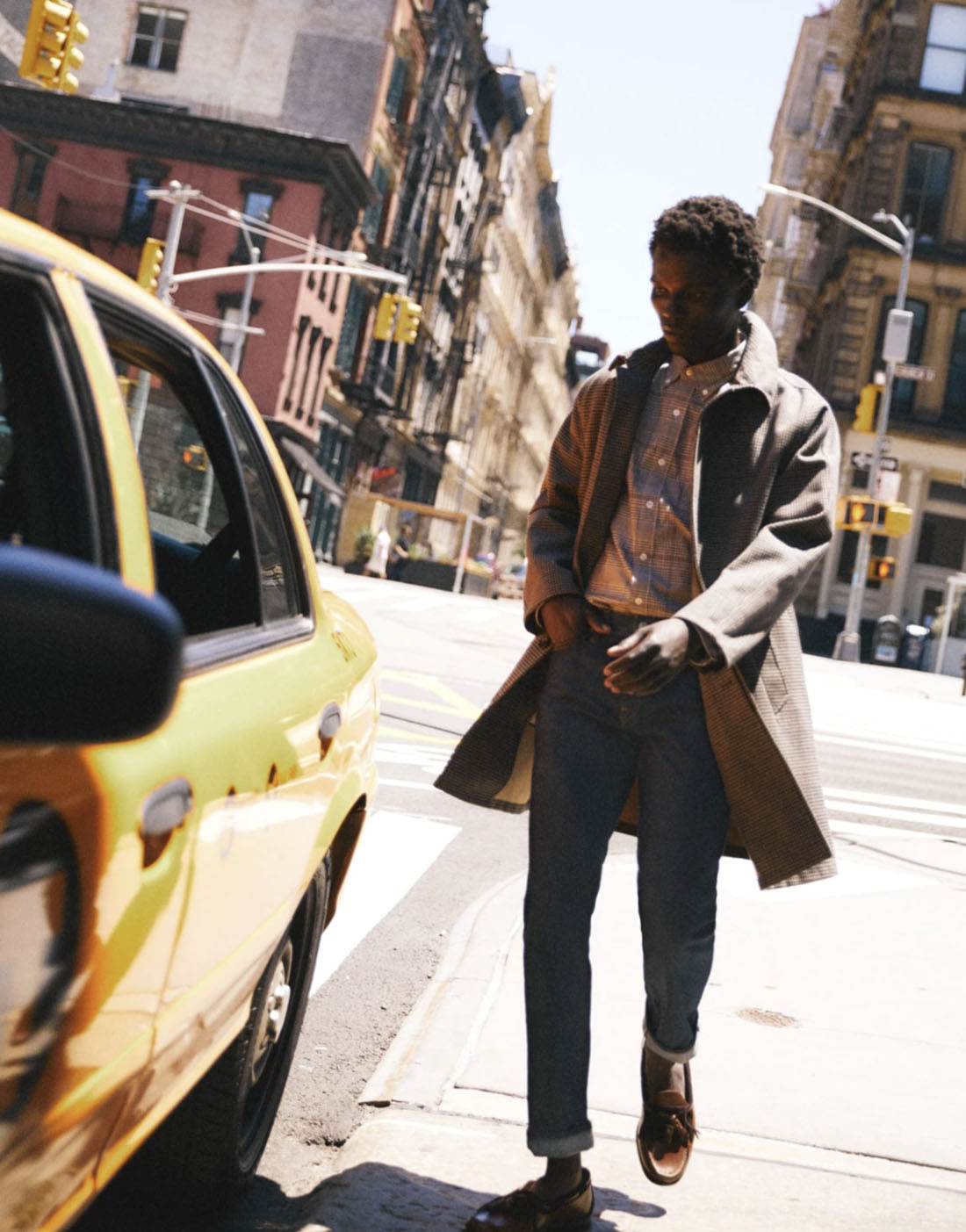 man standing on a sidewalk next to a yellow cab car