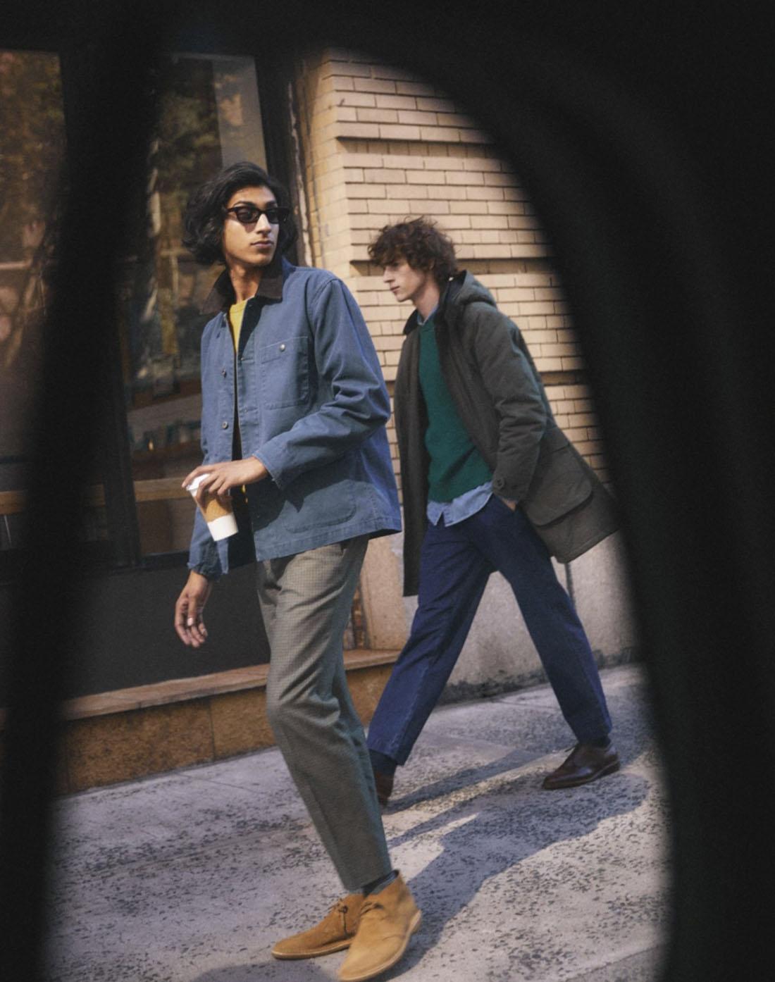 man wearing a blue coat jacket walking on sidewalk