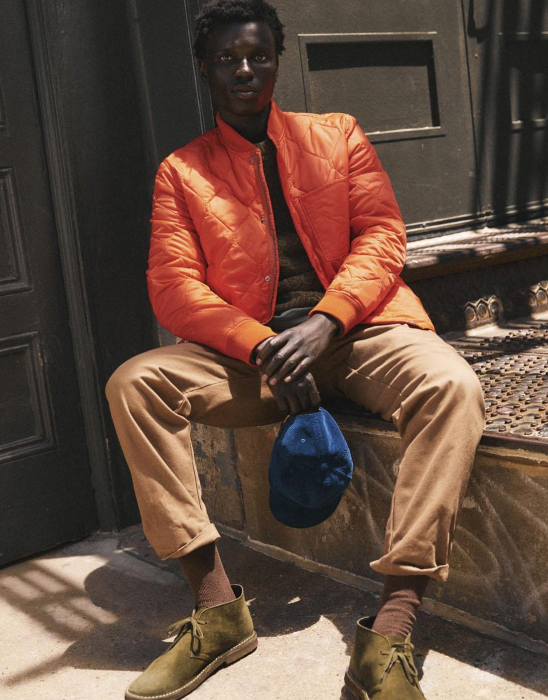 man sitting down wearing an orange jacket khaki pants and holding a blue hat