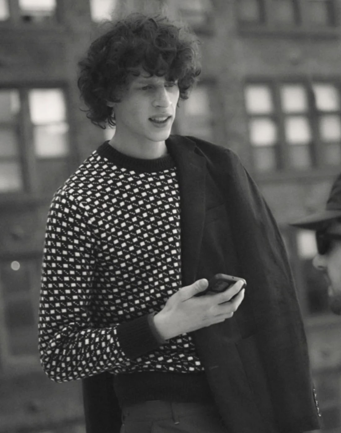black and white image of a man wearing a dot printed sweater